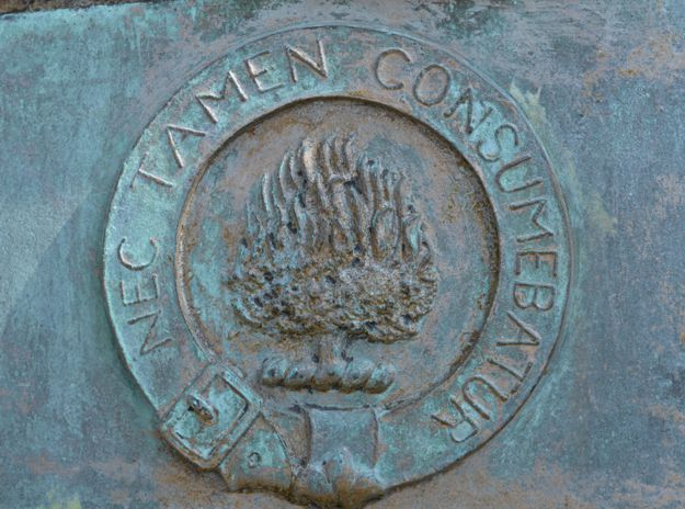 Bronze plaque detail: The burning bush with the motto NEC TAMEN CONSUMEBATUR (And yet it was not consumed)